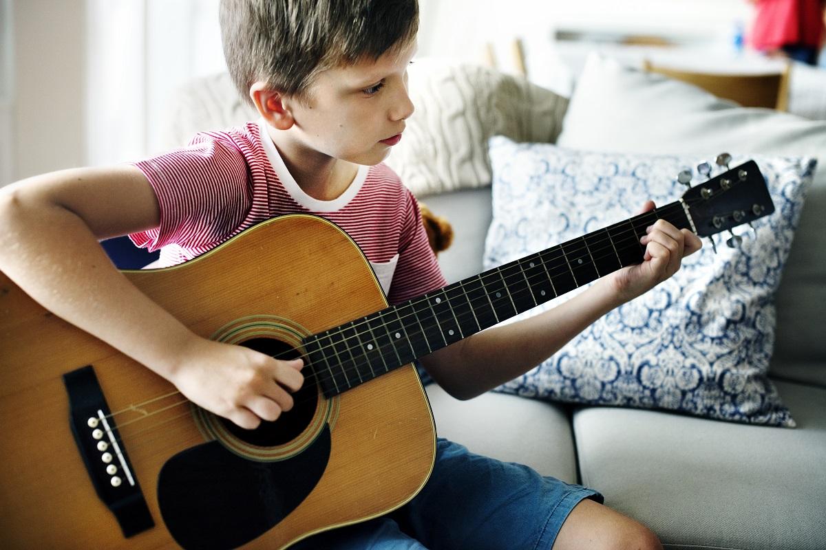 Junge sitzt auf einem Sofa und spielt Gitarre
