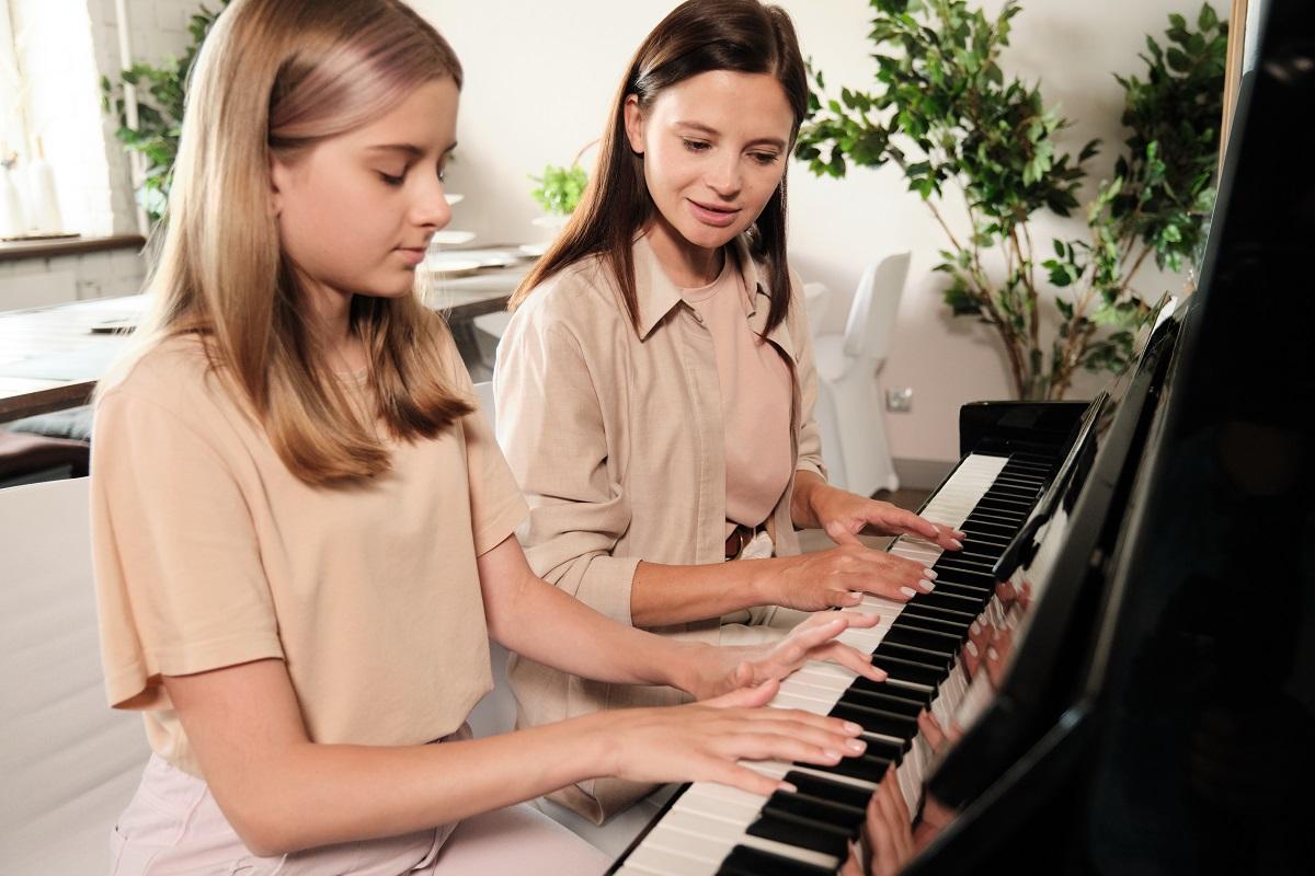 Mädchen bekommt Klavierunterricht von einer Lehrerin