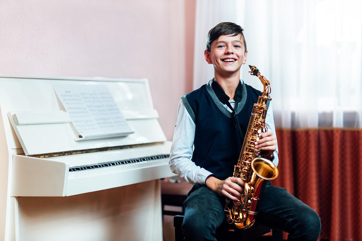 Junge sitzt vor einem Klavier und spielt Saxofon