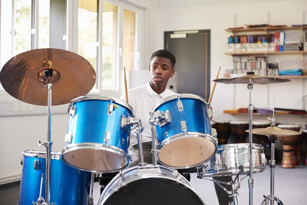 Dunkelhäutiger Junge spielt Schlagzeug